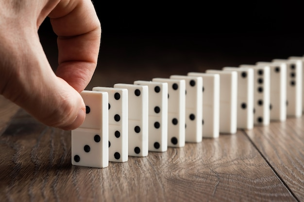Male hand pushing white dominoes