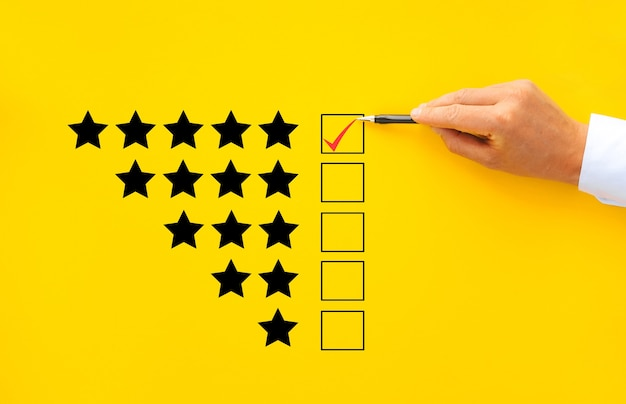 Male hand putting check mark a checkbox on five star rating. increase rating company concept.