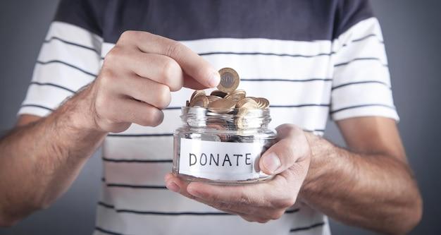 寄付の瓶にコインを入れる男性の手。
