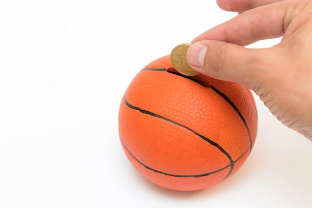 Мужская рука кладет монету евро в копилку с формой баскетбольного мяча на белом фоне