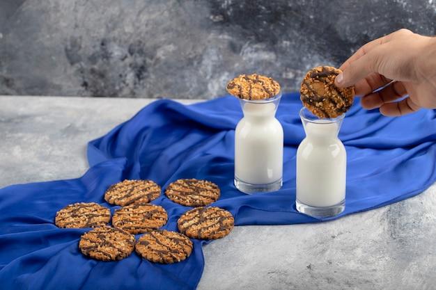 ミルクのガラスピッチャーにオートミールクッキーを入れている男性の手。