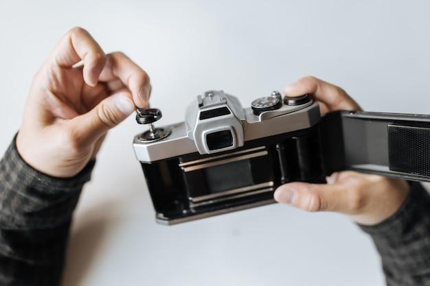 男性の手が白いテーブルにフィルムレトロなカメラをリロードします。横型
