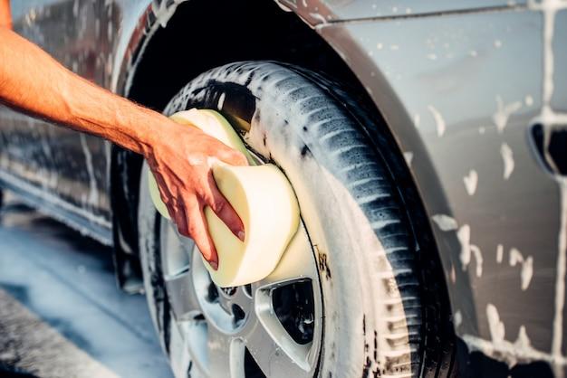 Мужская рука натирает колесо автомобиля пеной, автомобиль в мыльной пене. автомойка