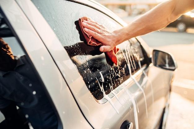 Мужская рука протирает окно автомобиля пеной, автомобиль в пене, автомойку. автомойка