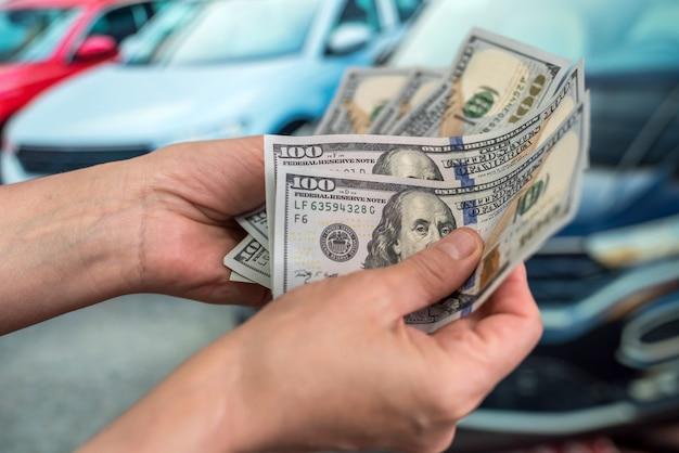 Autohouse에서 차를 사기 위해 달러를 보여주는 남성 손. 재원