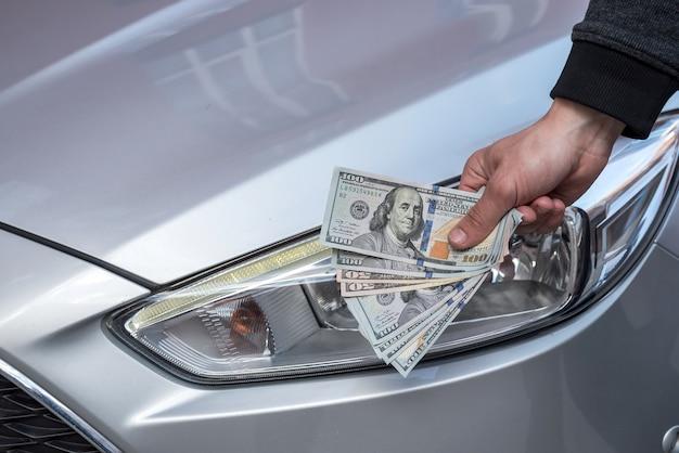自動車屋で車を買うためのドルを示す男性の手。ファイナンス
