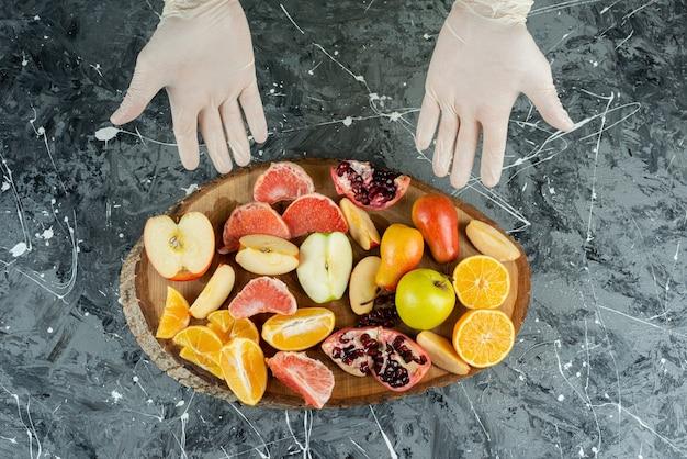 大理石のテーブルに新鮮な果物の束を示す男性の手。