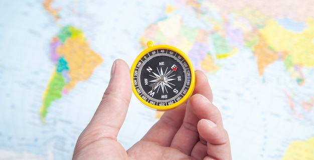 세계 지도 배경에 나침반을 보여주는 남성 손.
