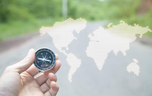 世界地図でコンパスを示す男性の手。