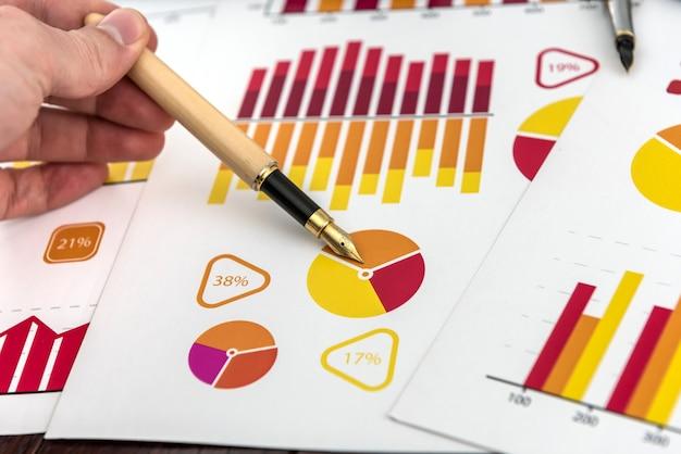 ペンで財務報告の図やチャートを示す男性の手。成長と成功