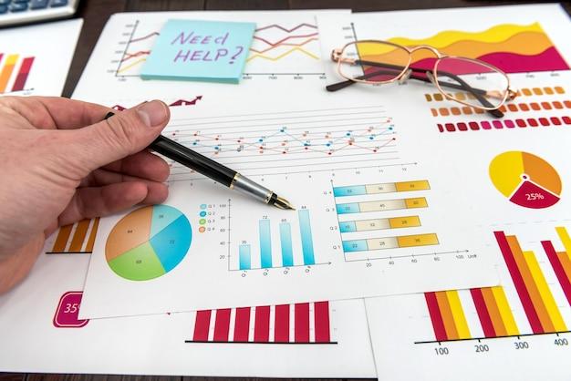 Мужская рука показывает диаграмму или диаграмму финансового отчета ручкой
