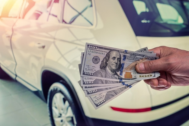 Male hand showing a dollar for buying a car in the autohouse. finance