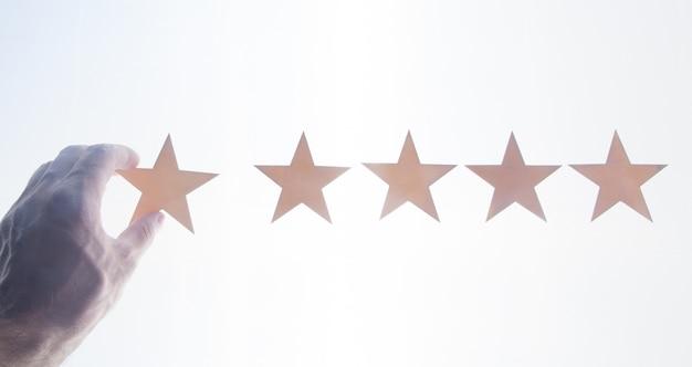 5つ星の評価を示す男性の手。