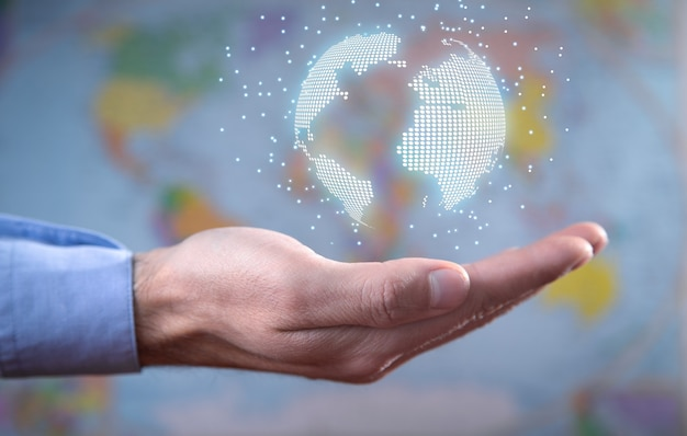Male hand showing globe on world map background.