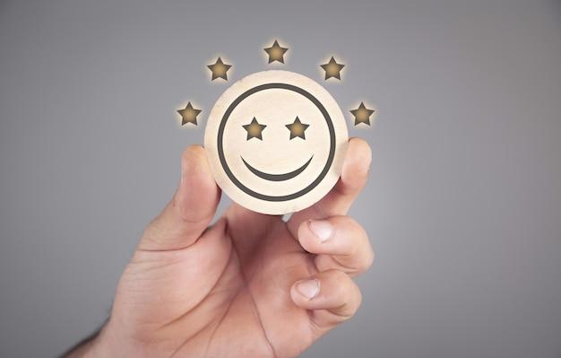 행복한 웃는 얼굴과 별 5개를 보여주는 남성 손. 고객 서비스 및 만족