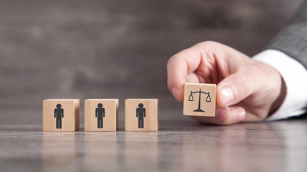 木製の立方体に裁判官の体重計と人間のアイコンを示す男性の手。