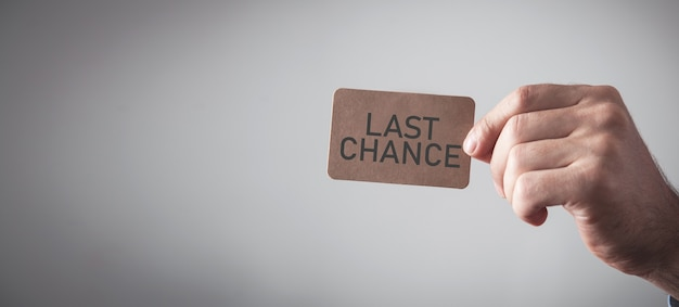Male hand showing last chance message on cardboard card.