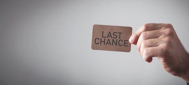 段ボールカードにラストチャンスメッセージを示す男性の手。