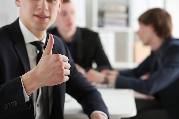 Мужская рука показывает знак ок или одобрения с большим пальцем руки вверх в офисе творческих людей во время конференции.