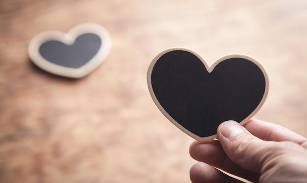 Мужская рука показывает деревянное сердце на деревянном столе.