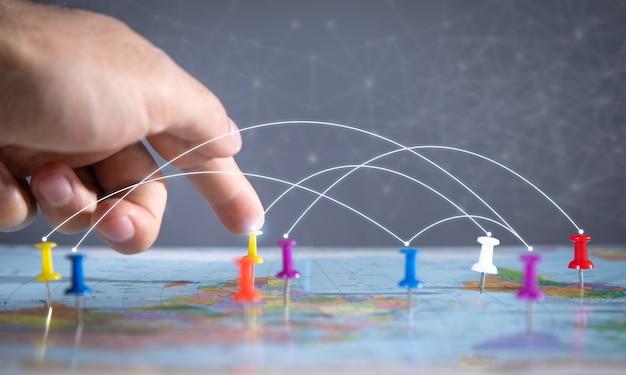 男性の手は世界地図に画鋲を示しています。通信網
