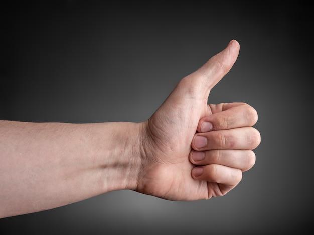 Мужская рука показывает большой палец вверх на серой стене.