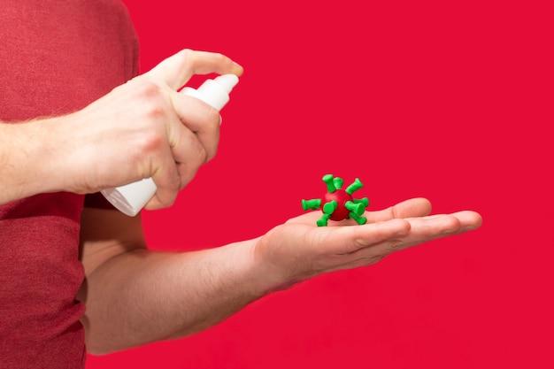 男性の手は、赤い背景で、covid-19インフルエンザウイルスの細胞に消毒剤をスプレーします。
