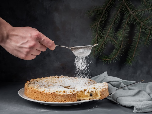 A male hand sprinkles powdered sugar on an apple pie standing on a table.