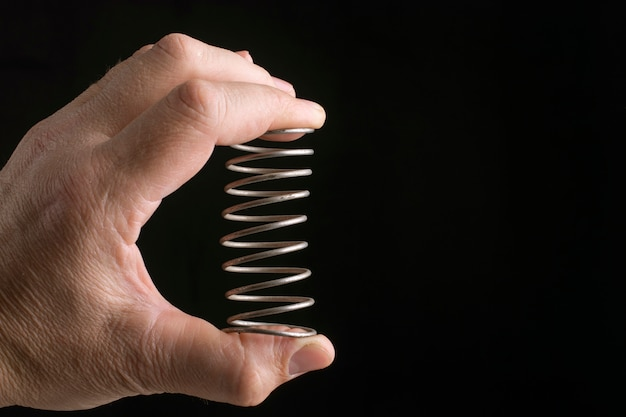 The male hand squeezes a metal spring on black