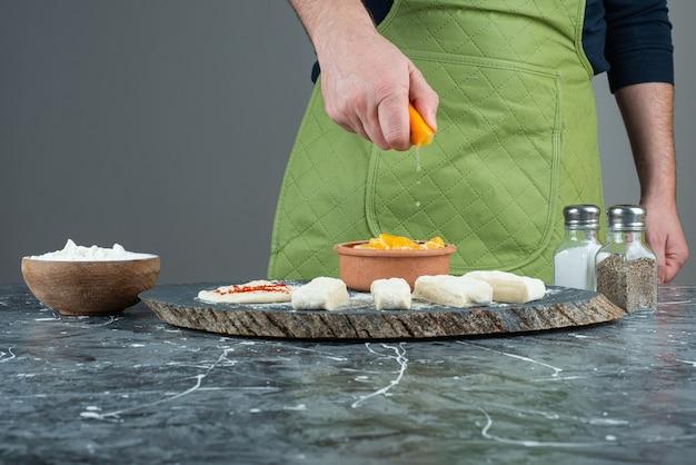 Mano maschio che spreme il succo di limone nei gamberetti sul tavolo di marmo.