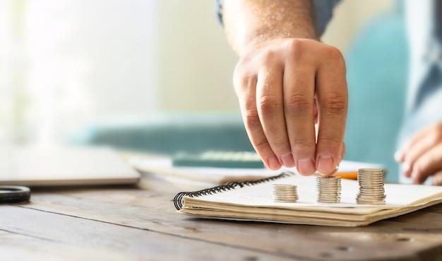 木製の机の上にコインを積み重ねる男性の手。住宅金融と予算の概念