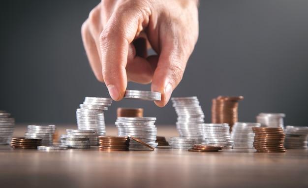 男性の手でコインを積み重ねます。お金を節約