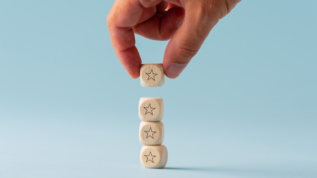Male hand stacking five wooden dices with star shape on them in a conceptual image.