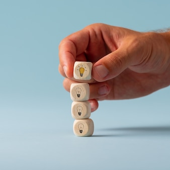 Male hand stacking wooden dices with light bulbs on them with the top one glowing yellow in a conceptual image. over blue background.