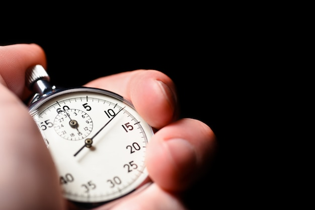 Male hand starts the analog stopwatch on a black background