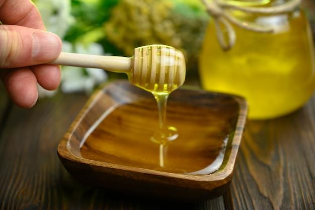 Мужская рука мешает мед деревянной ложкой
