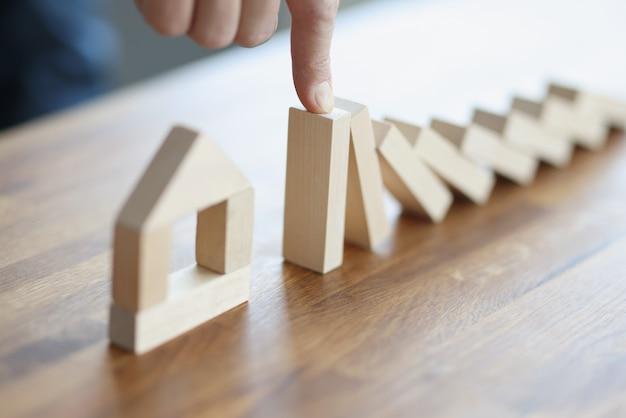 Мужская рука останавливает падение деревянных блоков на игрушечный домик крупным планом
