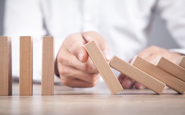 Male hand stopping wooden domino. business. crisis. risk
