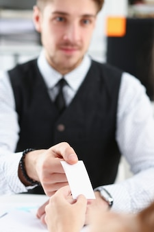 Male hand in suit give blank calling card to visitor