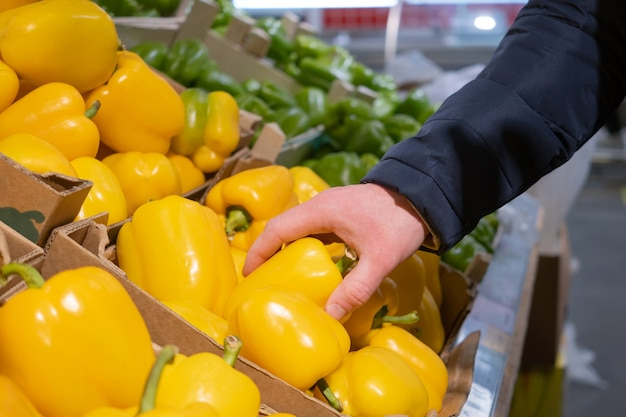 A male hand takes a yellow pepper from a box of peppers in a supermarket.
