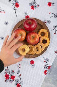 나무 접시에서 사과 반지를 복용하는 남성 손.