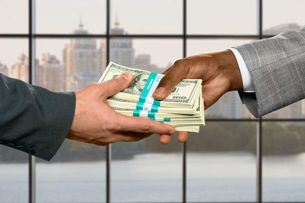 大きなお金を取る男性の手。都市の背景での送金。強力なリーダーの継承。クレジットで不動産を購入する。