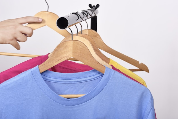 Male hand taking a hanger for clothes from shelf