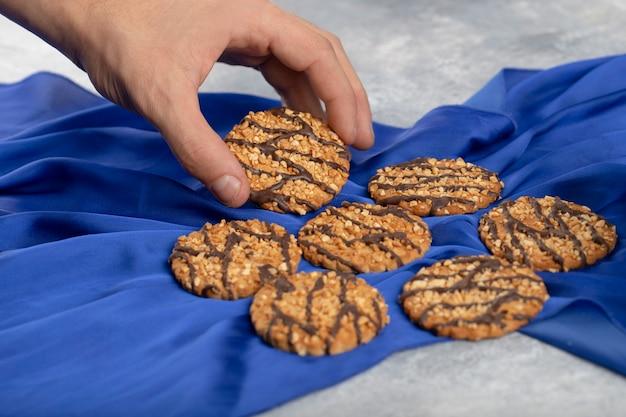 青いテーブルクロスの上に置かれたオートミールクッキーを取る男性の手。
