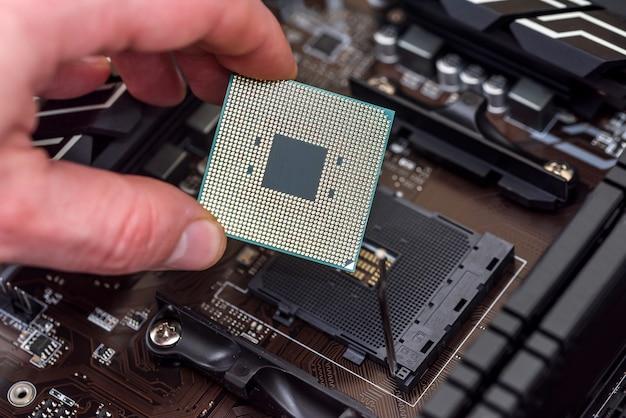 Мужская рука снимает чип процессора с материнской платы