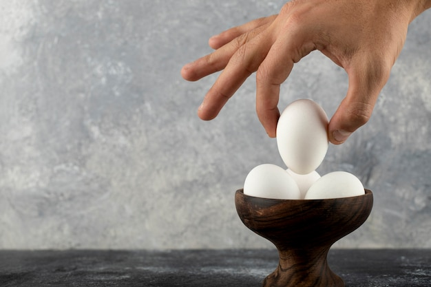 Male hand taking raw egg from wooden bowl.