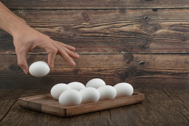 Male hand taking raw organic egg from wooden board.