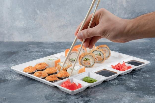 Mano maschio che prende il rotolo di sushi con le bacchette dal piatto bianco