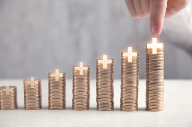Male hand touching in plus symbol. stack of coins