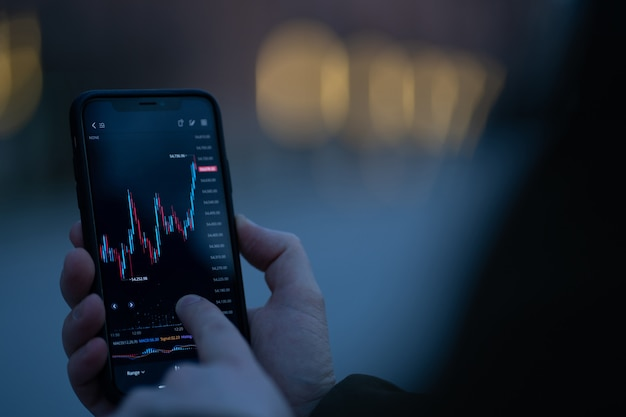 Male hand touching smartphone screen with real time forex chart while standing outdoors, selective focus on mobile phone with financial graph. trader checking stock market data in mobile app